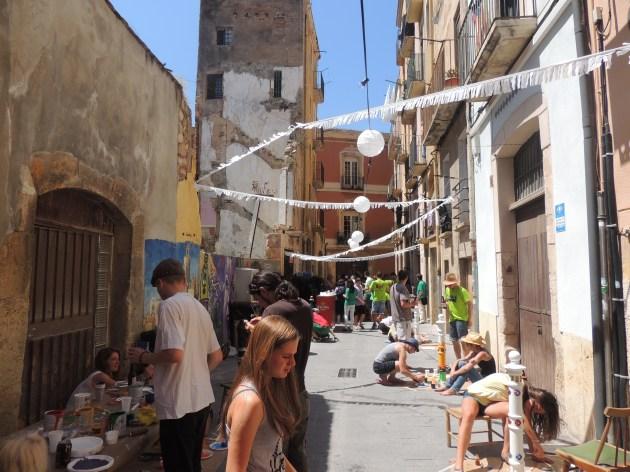 Imatge del carrer mentre la gent pinta els pilons.