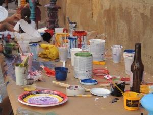 Una taula repleta de pots i estris per pintar.